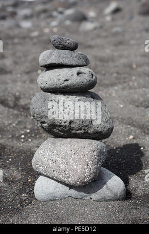 Balanced stacked stones or pebbles on a black sand beach. - Stock Photo