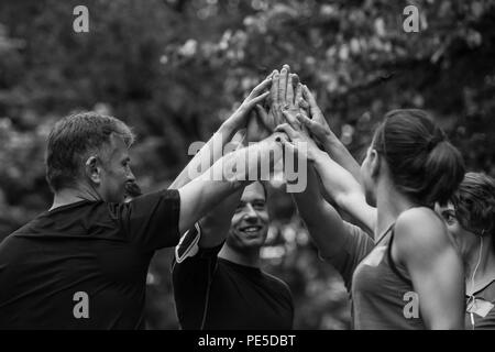 Group of healthy runners giving high five to each other while celebrating success after a training session. - Stock Photo