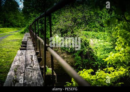 Old canal bridge leading away. - Stock Photo