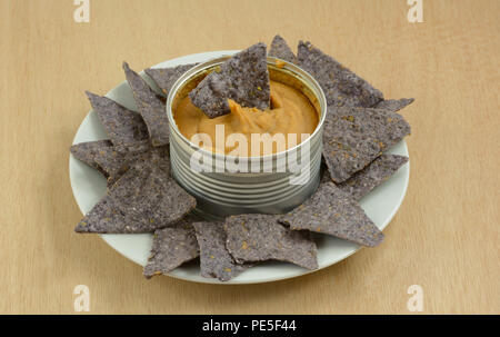 Warm canned bean dip heated on stove in can with blue corn tortilla chips on white snack plate - Stock Photo