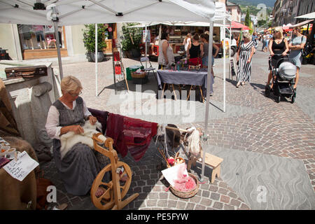woman spins threads with spinning wheel on market in swiss town of Sion - Stock Photo
