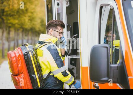 Emergency doctor using radio of ambulance - Stock Photo