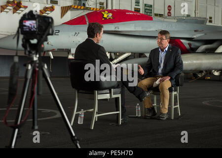 Secretary of Defense Ash Carter answers questions as he is interviewed by reporter Bob Woodruff while he and Malaysian Minister of Defense Hishammuddin Hussein visit the USS Theodore Roosevelt Nov. 5, 2015. (Photo by Senior Master Sgt. Adrian Cadiz)(Released) - Stock Photo