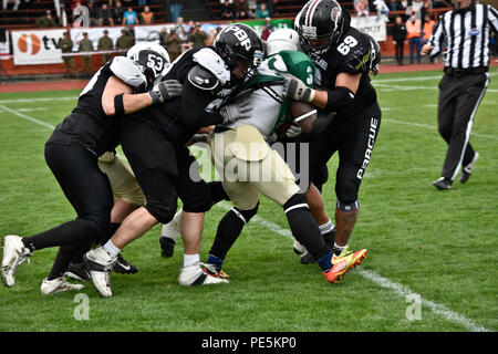 Sgt. Henry Ofori, a running back from the 2nd Cavalry Regiment's football team, runs the ball as four defensive players from the Prague Black Panthers attempt to tackle him during their game in Cesky Krumlov, Czech Republic, Sept. 26, 2015. The team participated in an American football game with the local Czech Republic semi-professional football team as the unit helped to commemorate the 70th anniversary of Cesky Krumlov's liberation during World War II while also demonstrating the U.S. commitment to their NATO and Czech allies. (U.S. Army photo by Sgt. William A. Tanner/released) - Stock Photo