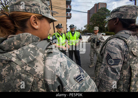 Senior Airman Kristine Rodriguez, left, Airman 1st Class Engel Placencia-Valdez, second from right, and Staff Sgt. Shaquan Williams, all with 108th Wing, New Jersey Air National Guard, coordinate with the Camden County Police Sept. 27, 2015. The joint New Jersey National Guard task force comprised of Soldiers with the 1st Squadron, 102nd Cavalry, and 108th Wing Airmen are assisting New Jersey civil authorities and the Delaware Port Authority with security during Pope Francis's visit to Philadelphia Sept. 26-27. (U.S. Air National Guard photo by Master Sgt. Mark C. Olsen/Released) - Stock Photo