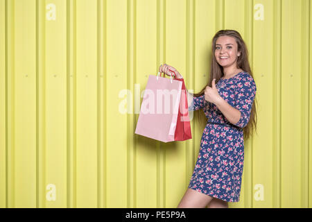 Portrait of happy girl showing thumbs up and holding shopping bags on yellow background. Summer shopping concept. - Stock Photo