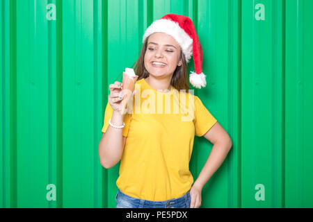 Portrait of beautiful young woman wearing santa hat and holding ice cream in cone on green background. - Stock Photo