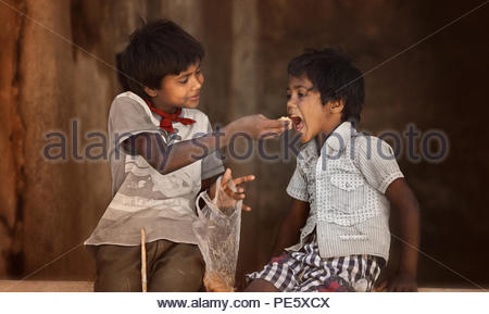 SARNESWAR, INDIA -MARCH 17, 2016: Unidentified poverty Boy gives food to his littel brother, about 32.7% percent of Indians are extremely poor yet, Sa - Stock Photo