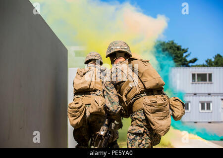 U.S. Marines and ROK Marines breach a building under smoke concealment during Korean Marine Exchange Program 15-12 at Gunha-Rhi, Gimpo, Republic of Korea, Sept. 17, 2015. KMEP 15-12 is a bilateral training exercise that enhances the ROK and U.S. alliance, promotes stability on the Korean Peninsula and strengthens ROK and U.S. military capabilities and interoperability. The ROK Marines are with 1st Company, 11th Battalion, 1st Regiment, 2nd Marine Division. The U.S. Marines are with Fox Company, 2nd Battalion, 3rd Marine Regiment, currently assigned to 4th Marine Regiment, 3rd Marine Division,  - Stock Photo