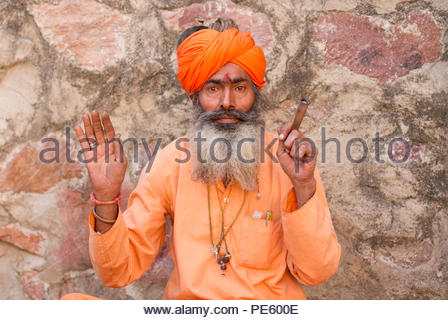 Haridwar, India - March 01, 2014: Portrait of an Indian sadhu wearing traditional attire by the sacred Ganges river in Haridwar, Uttarakhand, India. - Stock Photo