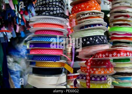 Stacks of multicoloured ribbons of various widths, patterns and textures in a craft market - Stock Photo