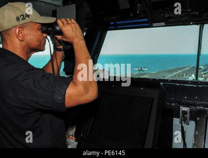151002-N-PG340-062  ARABIAN GULF (Oct. 2, 2015) Lt. Cmdr. Eric Cottrell looks for contacts while standing the officer of the deck watch on the bridge aboard the aircraft carrier USS Theodore Roosevelt (CVN 71). Theodore Roosevelt is deployed in the U.S. 5th Fleet area of operations supporting Operation Inherent Resolve, strike operations in Iraq and Syria as directed, maritime security operations and theater security cooperation efforts in the region. (U.S. Navy photo by Mass Communication Specialist 3rd Class Stephane Belcher/Released) - Stock Photo