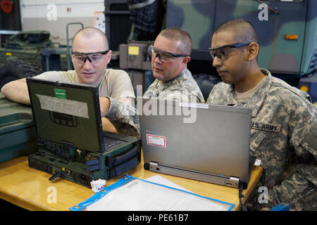 (From left) Arizona Army National Guard Spc. Jacob D. Rhodes, Sgt. 1st Class Justin M. Gregg and Pvt. John Ames with the 3666th Support Maintenance Company in Phoenix, trouble shoot a maintenance issue using a rugged computer called a Maintenance Support Devise Version 3 (MSDv3) Sept. 18, 2015 at Camp Dodge Joint Maneuver Training Center in Johnston, Iowa.  The Soldiers, who are wheeled vehicle mechanics, had the opportunity to work on different vehicle maintenance issues during their 15-day annual training at Camp Dodge. (U.S. Army National Guard photo by Staff Sgt. Brian A. Barbour) - Stock Photo