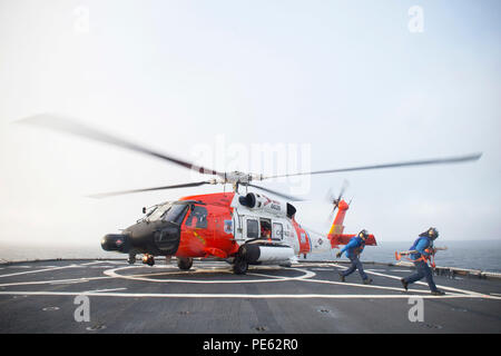 An HH-60 Jayhawk rescue helicopter from Coast Guard Air Station Kodiak in Kodiak, Alaska lands on the flight deck of Coast Guard Cutter Healy, Oct. 7, 2015, while underway in the southern Arctic Ocean. Healy is underway in the Arctic Ocean in support of the National Science Foundation-funded Arctic GEOTRACES, part of an international effort to study the distribution of trace elements in the world's oceans. (U.S. Coast Guard photo by Petty Officer 2nd Class Cory J. Mendenhall) - Stock Photo