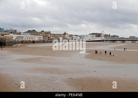 Weston-super-Mare, UK. 12th August, 2018. UK weather: after many hours of rain, a dry but overcast and breezy Sunday afternoon failed to bring many holidaymakers onto the beach, with some of those who did venture out wearing coats. Keith Ramsey/Alamy Live News - Stock Photo