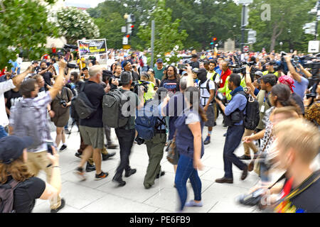 Washington D.C., USA. 12th August, 2018.  An alt-right supporter leaves the 'Unite the Right 2' rally in Lafayette Park to a crowd of counterprotesters and photographers.  Dressed in a Trump 2020 t-shirt, the man is attempting to leave the rally while people are shouting at him.  The photo was taken before he sought police protection nearby.  Credit: Mark Kanning/Alamy Live News. - Stock Photo