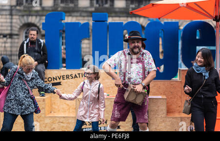 Edinburgh, Scotland UK. 13th August 2018. A street performer entertains tourists in the rain and drizzle on the Royal Mile in the Old Town of Edinburgh. Credit: Ben Collins/Alamy Live News - Stock Photo