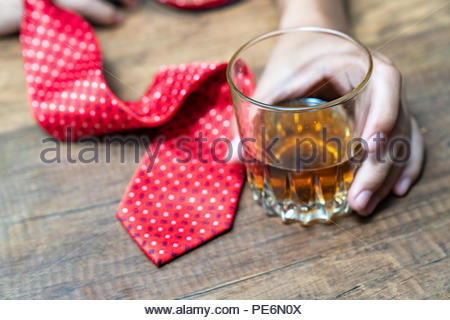 Drunk woman holding an alcoholic drink and sleeping with her head on the table (Focused on the drink, her face is out of focus) - Stock Photo