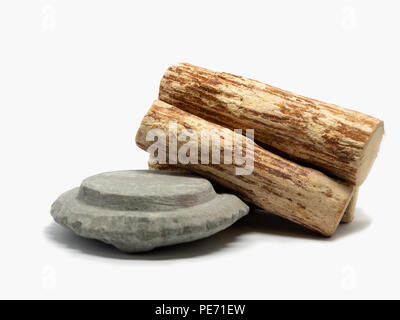 Thanaka wood and Kyauk pyin stone slab on white background (Isolated background). The Tanaka is popular with Burmese women. The face to make a beautif - Stock Photo