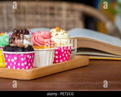 Colorful of homemade cupcake on wooden tray on and open book on wooden table. Concept of lifestyle and relax. - Stock Photo