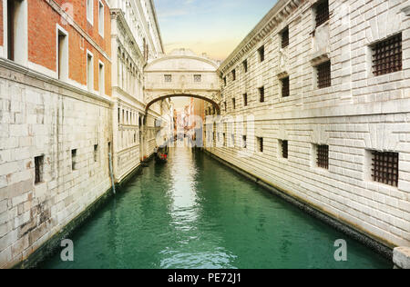 Venice, Italy, Jun 8, 2018: View of bridge of sighs with gondoliers carrying tourists in their gondolas in Venice, italy at sunset - Stock Photo