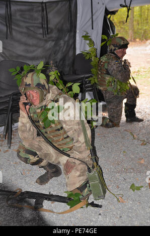 Soldier is using radio for communication during military operation