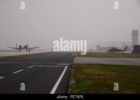 Two A-10 Thunderbolt IIs from the 25th Fighter Squadron taxi along the runway of Osan Air Base, Republic of Korea, Oct. 16, 2015, while an HH-60 Pavehawk assigned to the 33rd Rescue Squadron from Kadena Air Base, Japan is prepped for take-off. The squadrons are participating in the combat search and rescue exercise, Exercise Pacific Thunder 15-02. (U.S. Air Force photo by Staff Sgt. Benjamin Sutton) - Stock Photo