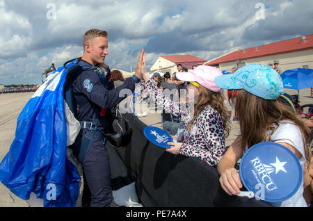 Jenna Koch (center), gives a high five to Cadet 1st Class Garrett Nobley, U.S. Air Force Academy Wings of Blue team member, during the 2015 Joint Base San Antonio Air Show and Open House Nov. 1, 2015, at JBSA-Randolph, Texas. Air shows allow the Air Force to display the capabilities of our aircraft to the American taxpayer through aerial demonstrations and static displays and allowing attendees to get up close and personal to see some of the equipment and aircraft used by the U.S. military today. (U.S. Air Force photo by Johnny Saldivar) - Stock Photo