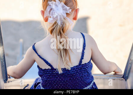 Cute little girl having fun on slide at a playground outdoors in summer. - Stock Photo