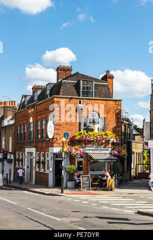 Customers drinking outside the historic Angel Inn in Highgate Village, London, UK during a heatwave - Stock Photo