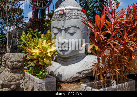 Stone statue of Sitting Buddha under the tree, with a garland in red and white colors of Indonesian flag for Indonesia Independence Day, Bali, Indones - Stock Photo
