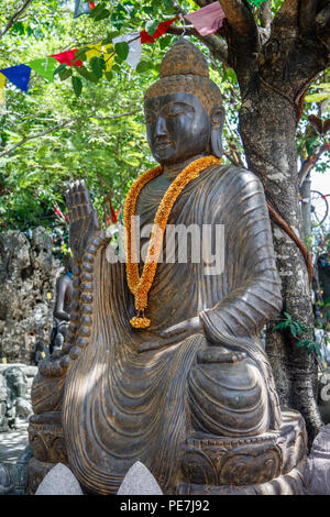 Stone statue of Sitting Buddha under the tree, Bali, Indonesia. Vertical image. - Stock Photo