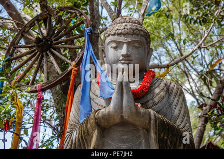 Stone statue of Sitting Buddha under the tree, Bali, Indonesia. - Stock Photo