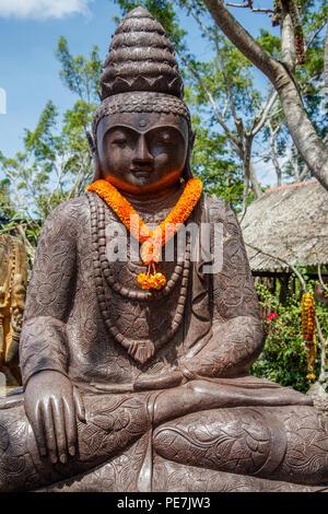 Stone statue of Sitting Buddha under the tree, Bali, Indonesia. Vertical image. - Stock Photo
