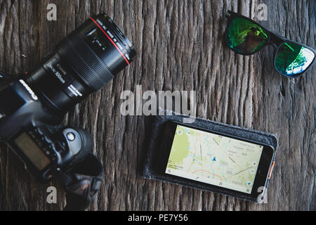 Top view accessories tourist man planning travel with mobile phone, camera map, sunglasses on wooden table. Summer vacation and Travel concept. - Stock Photo