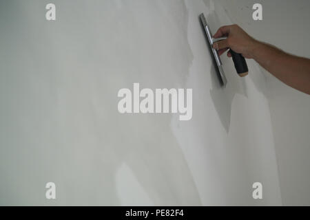 worker applying decorative concrete plaster on the wall, shallow focus - Stock Photo