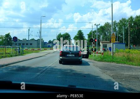 A car waiting at a railway level crossing in Lubliniec, Poland EU - Stock Photo