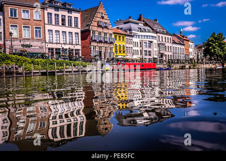 Lansdape view of the old town of Ghent in northern Belgium, with traditional buildings in the background and the river in the foreground - Stock Photo