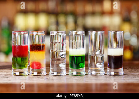 Multi-layer cocktails for a party, colorful cocktails for entertainment in a nightclub - Stock Photo