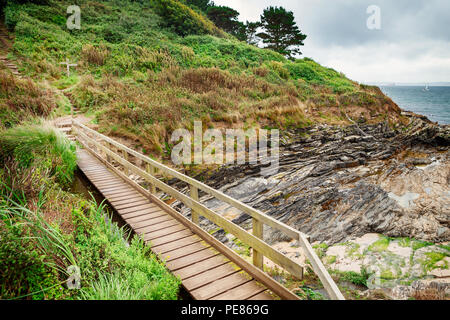 South west coastal path, bridge across secluded cove at St Antony's head, Roseland Penisula, Cornwall, - Stock Photo