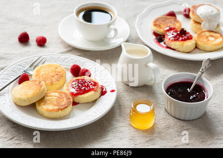 Cottage cheese pancakes with jam, honey and sour cream. Syrniki, sirniki. Russian, Ukrainian cuisine. Healthy tasty breakfast on table covered with li - Stock Photo