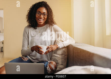Smiling woman in fashionable torn jeans holding a coffee cup while working on laptop computer at home. Businesswoman sitting on sofa at home and worki - Stock Photo