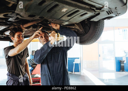 Mechanic fixing the car with coworker pointing and smiling. Two auto repair men working under a lifted vehicle in garage. - Stock Photo
