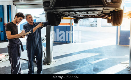 Two car mechanics in uniform examining the car and making notes for the repairs to be done. Mechanic making list of car malfunctions. - Stock Photo