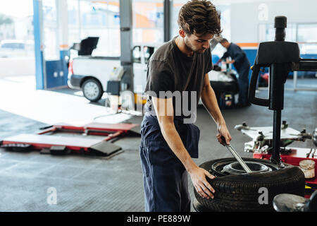 Repairman replacing tire on wheel in workshop. Mechanic changing car tire in service station. - Stock Photo