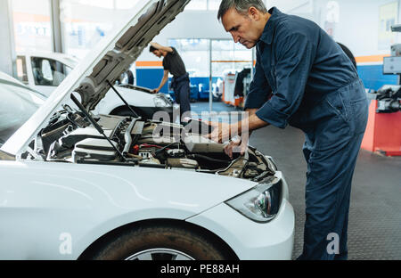 Car mechanic with diagnostic device for reading the error codes. Mechanic checking the car in service station. - Stock Photo
