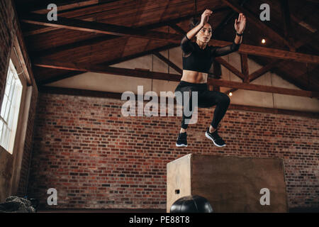 Shot of a young woman jumping onto a box as part of exercise routine. Fitness woman doing box jump workout at gym. - Stock Photo