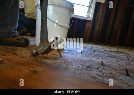 A disaster relief volunteer pulls a nail out of the subfloor of a house affected by the flood in Sumter, S.C., Oct. 19, 2015. The main focus for volunteers from Shaw Air Force Base, S.C., and the Southern Baptist Convention disaster relief team from Kentucky was to remove the mold from the house, including in the wood floors, and to kill any remaining mold preventing new mold from growing. (U.S. Air Force photo by Senior Airman Diana M. Cossaboom/Released) - Stock Photo