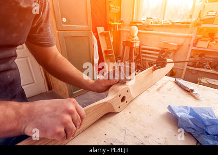 Close up of A man carpenter in a cap, goggles and a T-shirt is sanding a wooden  in the workshop, in the background a lot of tools - Stock Photo