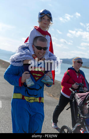 A family races to the finish line during a Superhero Fun Run on the Seawall at Marine Corps Air Station Iwakuni, Japan, Oct. 31, 2015. The 1.5K run allowed station residents to celebrate the Halloween festivities while being physically active. Snacks and beverages waited at the finish line as participants crossed. Once bellies were filled, families had the opportunity to take their photos with an outline of a comic-style city backdrop. (U.S. Marine Corps photo by Sgt. Antonio J. Rubio/Released) - Stock Photo